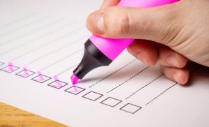 Checking off Items on a list for the home buying process with a pink highlighter