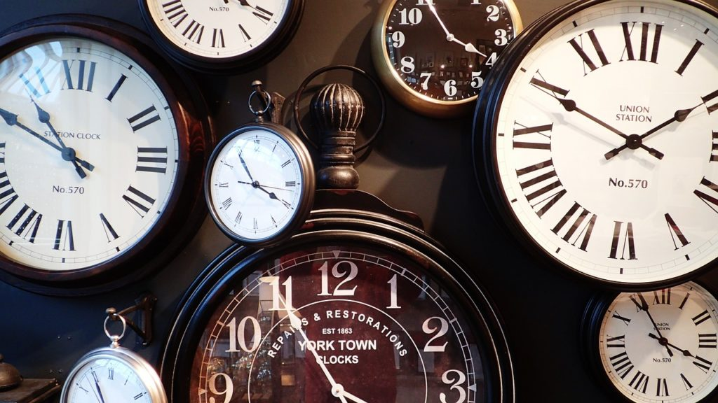 many clock faces in different colors show importance of time management in real estate