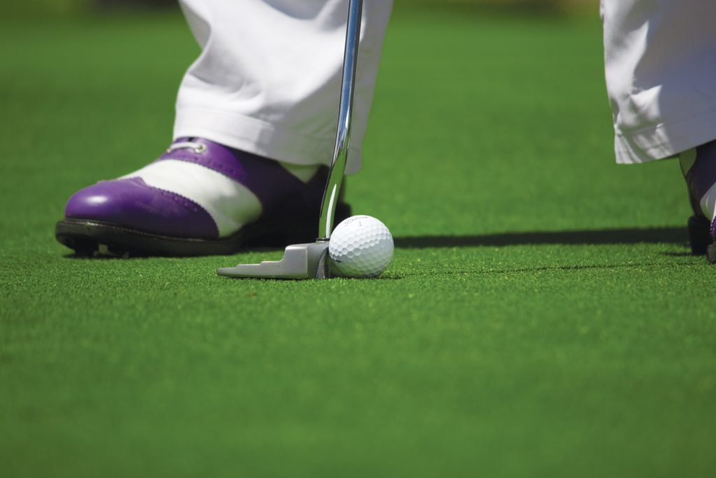 golf green, golf club & golf ball and golfer in purple & white shoes | senior living amenities