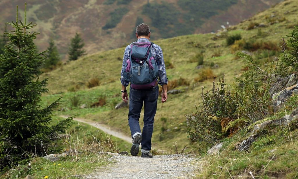 Man hiking a wilderness trail wearing a backpack | Active Adult Communities near recreation
