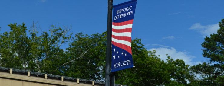 acworth centennial banner on light pole against blue sky
