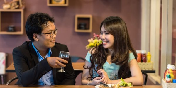 asian couple enjoying a meal & wine
