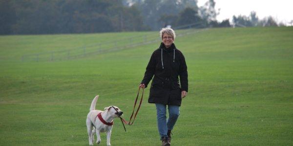 smiling woman walking dog in field
