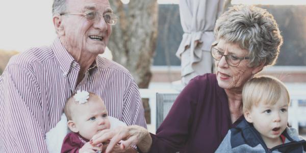 Grandparents holding grandchildren slider