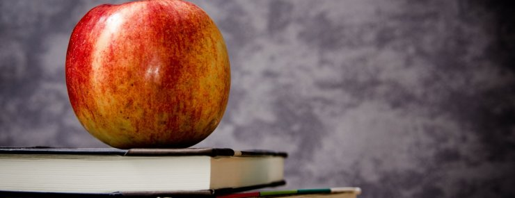 red yellow and green apple sitting on top of stack of 3 books against chalkboard background