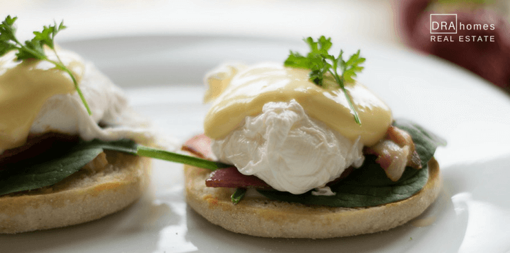 Open faced english muffin with poached eggs on white plate | DRA Homes Real Estate watermark