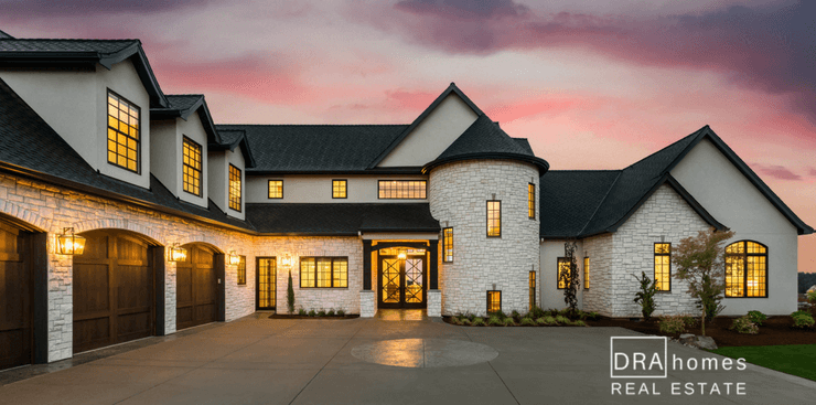 Luxury Home at sunset with lights glowing through windows | DRA Homes Real Estate Logo